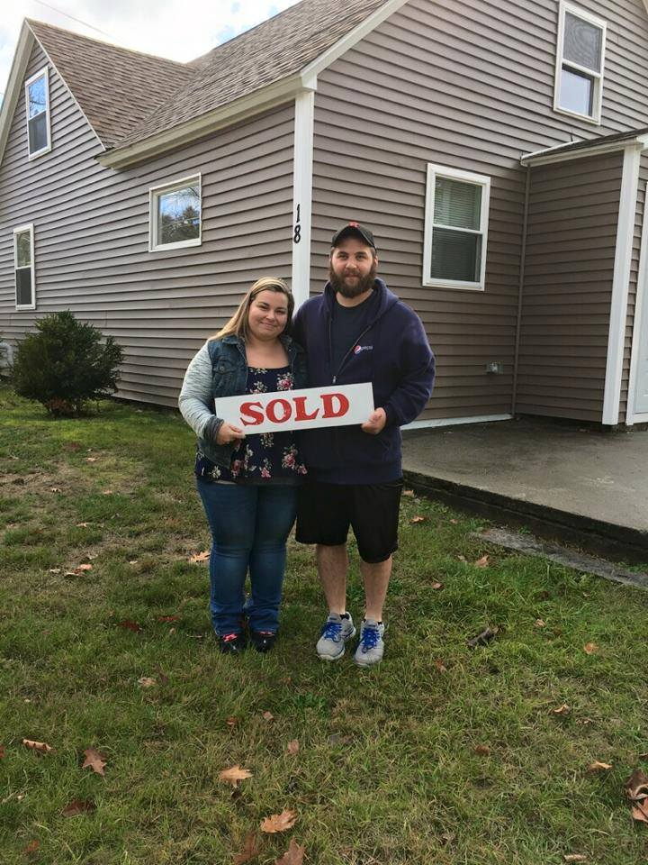 the best closings couple standing in front of their new house